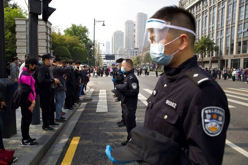 (AP Photo/Ng Han Guan). People and policemen bow their heads during a national moment of mourning for victims of coronavirus in Wuhan in central China's Hubei Province, Saturday, April 4, 2020. With air raid sirens wailing and flags at half-staff, Chin...
