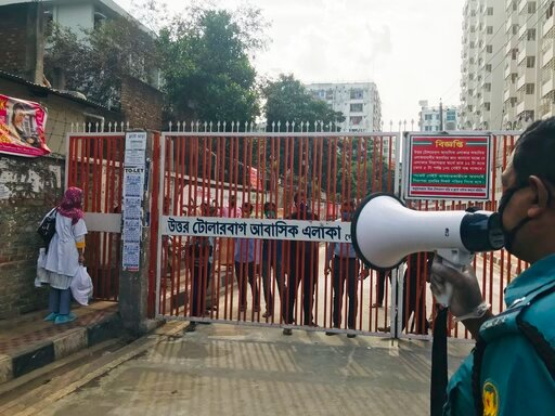 (AP Photo/Al-emrun Garjon). In this Monday, March 23, 3030 photo, a policeman urges residents not to come out of their homes as residents stand behind a gate, hours after the second death from COVID-19 was confirmed from the area, in Dhaka, Bangladesh....
