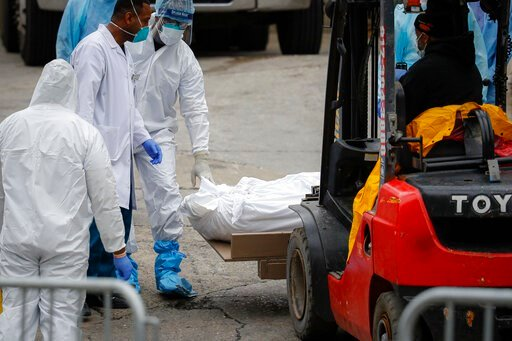 (AP Photo/John Minchillo). A body wrapped in plastic is prepared to be loaded onto a refrigerated container truck used as a temporary morgue by medical workers due to COVID-19 concerns, Tuesday, March 31, 2020, at Brooklyn Hospital Center in the Brookl...