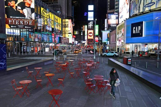 (AP Photo/Seth Wenig). In this March 16, 2020 file photo, a woman walks through a lightly trafficked Times Square in New York, March 16, 2020. As of Sunday, nearly 2,000 people with the virus have been hospitalized in the state of New York and 114 have...