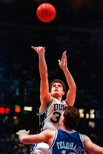 (AP Photo/Charles Arbogast, File). FILE - In this March 28, 1992, file photo, Duke's Christian Laettner takes the winning shot in overtime over Kentucky's Deron Feldhaus for a 104-103 victory in the East Regional final NCAA college basketball game in P...