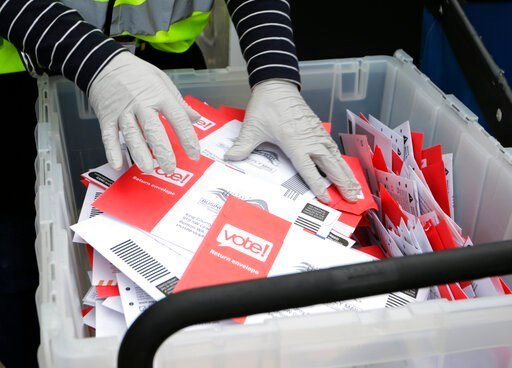 (AP Photo/John Froschauer, File). FILE - In this March 10, 2020, file photo wearing gloves, a King County Election worker collect ballots from a drop box in the Washington State primary, in Seattle. But the 2020 presidential election is creeping ever c...