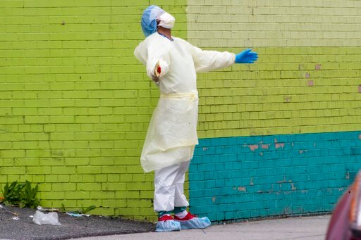 (AP Photo/Mary Altaffer). A medic of the Elmhurst Hospital Center medical team reacts after stepping outside of the emergency room, Saturday, April 4, 2020, in the Queens borough of New York. The new coronavirus causes mild or moderate symptoms for mos...