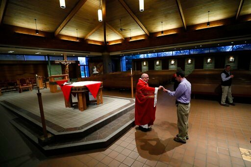 (AP Photo/Charlie Neibergall). The Rev. Michael Amadeo, left, gives Holy Communion during the broadcast and recording of the Palm Sunday Mass at Our Lady's Immaculate Heart Catholic Church for parishioners to watch online Saturday, April 4, 2020, in An...