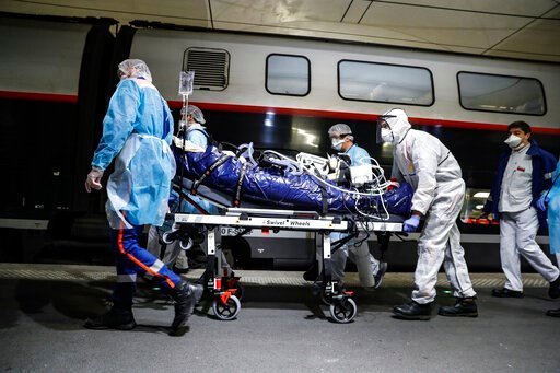 (Thomas Samson, Pool via AP). Medical staff embark a patient infected with the COVID-19 virus in a train at the Gare d'Austerlitz train station Wednesday April 1, 2020 in Paris. France is evacuating 36 patients infected with the coronavirus from the Pa...