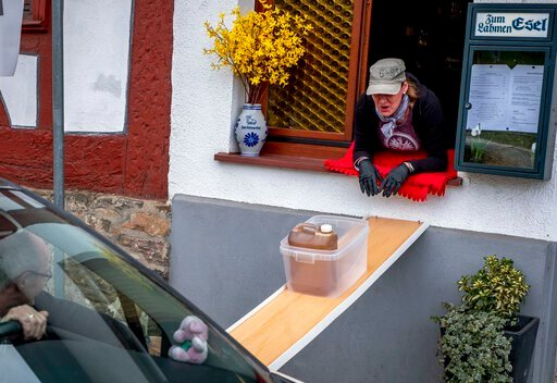 (AP Photo/Michael Probst). A can with apple cider slides down to car from a window of the apple cider restaurant 'Zum Lahmen Esel' in Frankfurt, Germany, Friday, April 3, 2020. Due to the coronavirus outbreak the restaurant which has been in operation ...