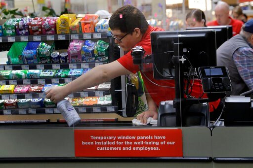 (AP Photo/Charlie Riedel, File). FILE - In this March 26, 2020, file photo, Garrett Ward sprays disinfectant on a conveyor belt between checking out shoppers behind a plexiglass panel at a Hy-Vee grocery store in Overland Park, Kan. From South Africa t...