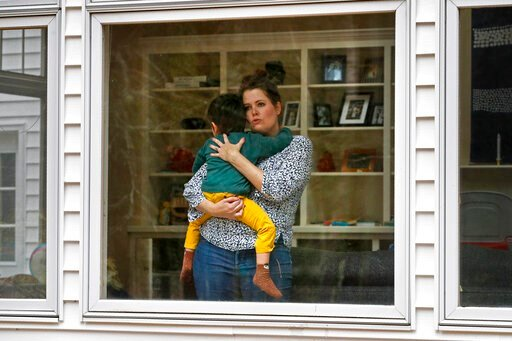 (AP Photo/Robert F. Bukaty). In this Wednesday, April 1, 2020 photo, Joy Engel holds her son at her home in Cape Elizabeth, Maine. Engel, who is pregnant, and her husband, Dr. Ben Hagopian, who works at a family practice and an urgent care clinic, deci...
