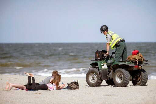 (Stephen B. Morton/Atlanta Journal-Constitution via AP). Georgia Department of Natural Resources Law Enforcement Division Corporal Barry Britt, right, enforces Gov. Bryan Kemp's order to open the beaches on Tybee Island, Ga., Saturday, April 4, 2020, a...