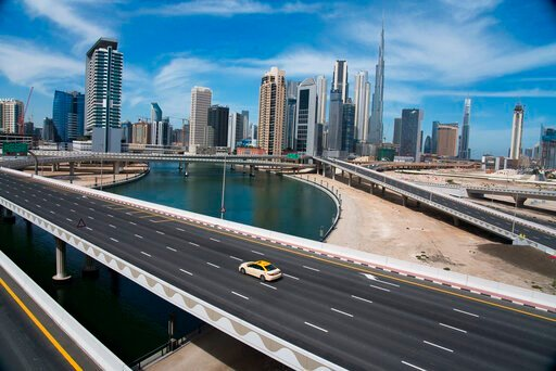 (AP Photo/Jon Gambrell). A lone taxi cab drives over a typically gridlocked highway with the Burj Khalifa, the world's tallest building, in the skyline behind it in Dubai, United Arab Emirates, Monday, April 6, 2020. Dubai, one of seven sheikdoms in th...