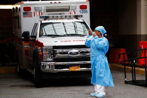(AP Photo/Kathy Willens). An emergency room nurse dons her face protectors after taking a break in a driveway for ambulances and emergency medical services vehicles outside Brooklyn Hospital Center's emergency room, Sunday, April 5, 2020, in New York, ...