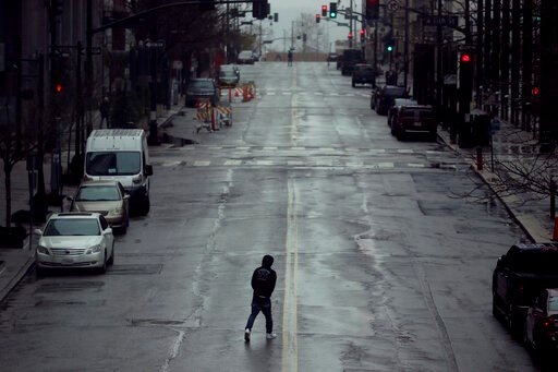(AP Photo/Charlie Riedel, File). FILE - In this April 3, 2020, file photo a man crosses an empty street in downtown Kansas City, Mo. Americans are increasingly taking preventative measures, including staying away from large crowds and avoiding touching...