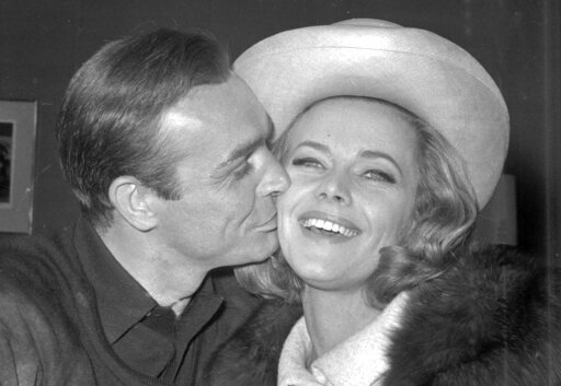 (AP Photo, FILE). FILE - In this B/W file photo dated March 25, 1964, British actor Sean Connery kisses actress Honor Blackman during a party at Pinewood Film Studios, in Iver Heath, England.  Blackman, the actor best-known for playing Bond girl Pussy ...