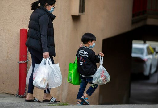 (AP Photo/Damian Dovarganes, File). FILE - In this April 2, 2020 file photo, an adult and a child, both wearing face masks amid the coronavirus outbreak, carry bags in the Chinatown neighborhood of Los Angeles. The first U.S. national data on COVID-19 ...