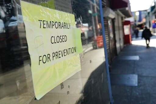 (AP Photo/Frank Franklin II, File). FILE - In this April 4, 2020, file photo, pedestrians pass closed stores on Roosevelt Avenue in the Queens borough of New York. The coronavirus crisis is upending service businesses, and the crisis may permanently ch...