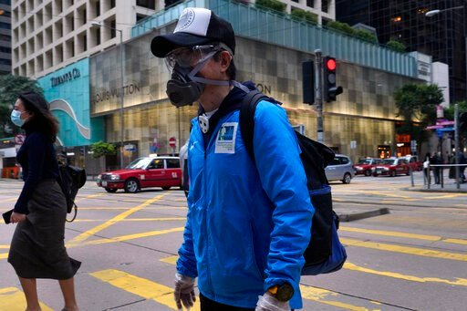 (AP Photo/Vincent Yu). People wearing face masks walk at a downtown street in Hong Kong Monday, April 6, 2020. The new coronavirus causes mild or moderate symptoms for most people, but for some, especially older adults and people with existing health p...