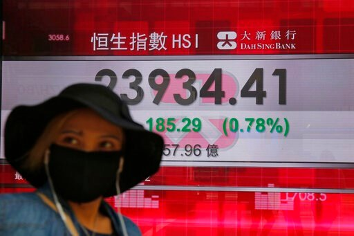 (AP Photo/Kin Cheung). A woman wearing a face mask walks past an electronic board showing Hong Kong share index outside a local bank in Hong Kong, Tuesday, April 7, 2020. Asian shares are rising, echoing the rally on Wall Street fueled by signs of hope...