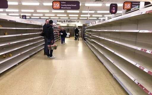 (AP Photo/Kirsty Wigglesworth, File). FILE - In this Thursday, March 19, 2020 file photo, people stand in an aisle of empty shelves in a supermarket in London,  amid panic-buying due to the coronavirus outbreak. A pandemic forcing everyone to stay home...