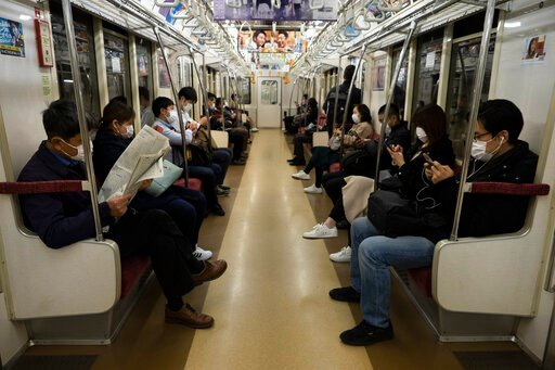 (AP Photo/Jae C. Hong). Commuters ride a train Tuesday, April 7, 2020, in Tokyo. Japanese Prime Minister Shinzo Abe said that he will declare a state of emergency for Tokyo and six other prefectures as early as Tuesday to bolster measures to fight the ...