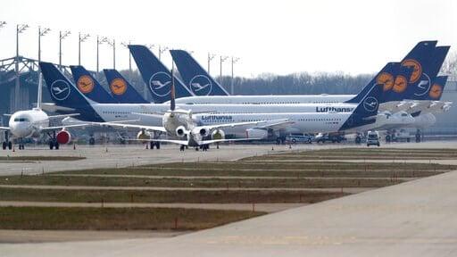 (AP Photo/Matthias Schrader). German Lufthansa planes sit parked in a line at the airport in Munich, Germany, Thursday, March 26, 2020. The planes are not in use because of the novel coronavirus outbreak. The new coronavirus causes mild or moderate sym...
