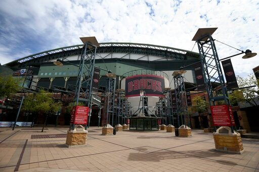(AP Photo/Ross D. Franklin, File). FILE - In this Thursday, March 26, 2020 file photo, The main entrance in front of Chase Field is devoid of activity in Phoenix. Putting all 30 teams in the Phoenix area this season and playing in empty ballparks was a...