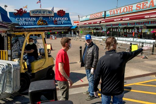 (AP Photo/Andrew Harnik). In this April 6, 2020, photo, Billy White, right, and his brother Sonny White, second from right, owners of Captain White Seafood City, along with their nephew Paul White, left, and Stan Kiser with Jessie Taylor Seafood, secon...