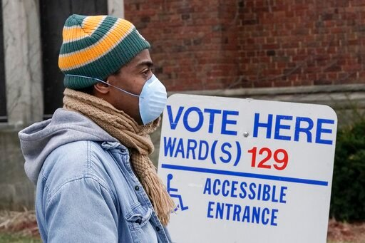 (AP Photo/Morry Gash). Voters masked against coronavirus line up at Riverside High School for Wisconsin's primary election Tuesday April 7, 2020, in Milwaukee. The new coronavirus causes mild or moderate symptoms for most people, but for some, especial...