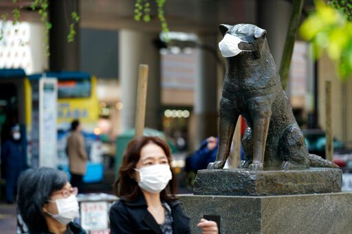 """(AP Photo/Eugene Hoshiko). A statue of a Japanese Akita dog named """"Hachiko"""" wearing a face mask is seen near Shibuya Station Wednesday, April 8, 2020, in Tokyo. Japanese Prime Minister Shinzo Abe declared a state of emergency on Tuesday for Tokyo and s..."""