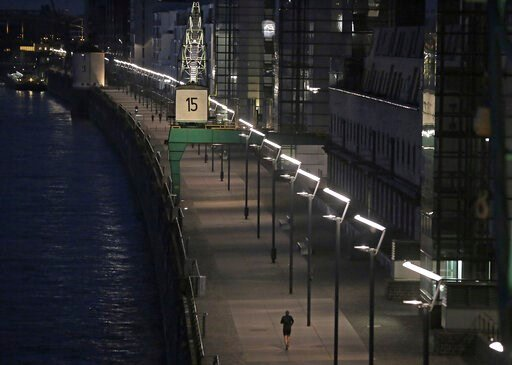 (Oliver Berg/dpa via AP). A man jogs in the morning in the Rheinauhafen in Cologne, North Rhine-Westphalia Wednesday, April 8, 2020. To contain the coronavirus, NRW has banned all accumulations of three or more people in public.