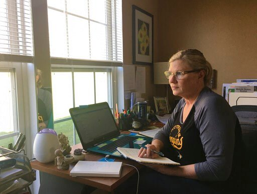 (Nick Bushée via AP). This April 3, 2020 photo shows realtor Michelle Bushée posing at her desk while working from her home in Pittsburgh, Pa. Bushee has always been an avid planner. Her weeks used to be very busy but now the entire month of April is e...
