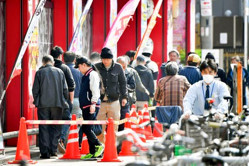 (Kyodo News via AP). People wait in line prior to the opening in front of a pachinko gaming parlor in Osaka, western Japan Wednesday morning, April 8, 2020. Japan's Prime Minister Shinzo Abe declared a month-long state of emergency Tuesday for Tokyo an...