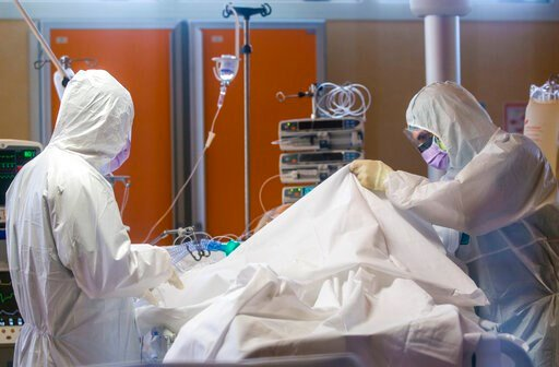 (AP Photo/Domenico Stinellis, File). FILE - In this March 25, 2020 file photo, medical staff tend to patients at the intensive care unit of the Casalpalocco COVID-19 Clinic on the outskirts of Rome. The pressures on intensive care units in Italy and Sp...