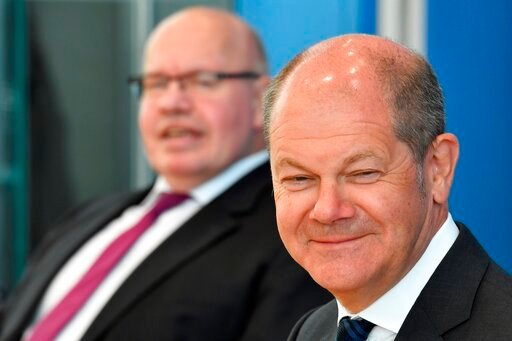 (John Macdougall/Pool via AP). German Economy Minister Peter Altmaier, left, and German Finance Minister and Vice-Chancellor Olaf Scholz arrive to give a press conference on an aid package in response to the COVID-19 coronavirus pandemic, in Berlin, Mo...