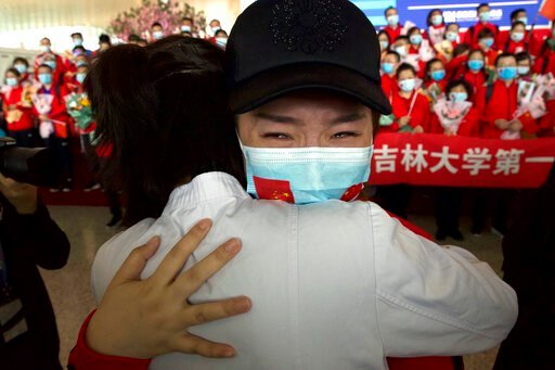 (AP Photo/Ng Han Guan). A medical worker from China's Jilin Province reacts as she prepares to return home at Wuhan Tianhe International Airport in Wuhan in central China's Hubei Province, Wednesday, April 8, 2020. Within hours of China lifting an 11-w...