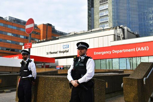 (Dominic Lipinski/PA via AP). Police officers stand outside St Thomas' Hospital in the background in central London, where Prime Minister Boris Johnson remains in intensive care as his coronavirus symptoms persist, Wednesday April 8, 2020. Johnson has ...