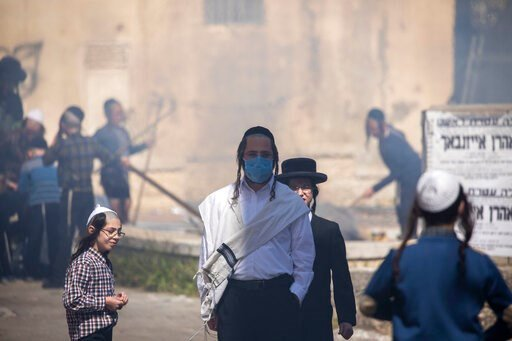 (AP Photo/Ariel Schalit). An ultra-Orthodox Jewish men wears a face mask as children burn leavened items in final preparation for the Passover holiday in the Orthodox neighborhood of Mea Shearim in Jerusalem, Wednesday, April 8, 2020. Jerusalem authori...