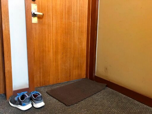 (AP Photo/Janelle Cogan). In this April 6, 2020, photo, shoes that are not allowed inside sit outside the door to Associated Press journalist Janelle Cogan's Atlanta home. Her boyfriend is an essential worker in the transportation sector, and because h...