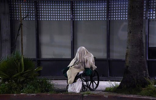 (AP Photo/Damian Dovarganes). A homeless person sits on a wheelchair under rainy weather on Sunset Blvd., in the Echo Park neighborhood of Los Angeles Monday, April 6, 2020. One population is particularly vulnerable to contracting and spreading the cor...