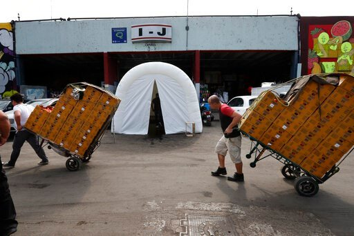 (AP Photo/Marco Ugarte). Workers pull dollies loaded with boxes of produce past a decontamination tent at the Centro de Abastos, the main food distribution center in Mexico City, Tuesday, April 7, 2020. The tent was set up a measure to help slow down t...