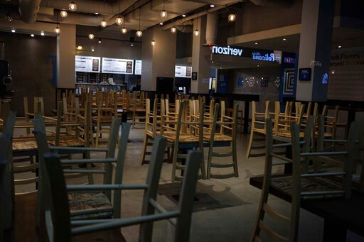 (AP Photo/Yuki Iwamura, File). FILE - In this March 16, 2020 file photo, chairs hang stacked on empty tables at a closed restaurant in New York.  Small business owners across the country waited again Wednesday, April 8,  to receive loan money under the...